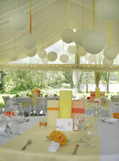 Outdoor catering event under a tent with handing orbs and formal table setting